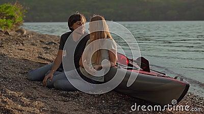 Ein junger Mann und eine junge Frau, die an einem großen aufblasbaren Kajak am Meer oder am See sitzt stock footage