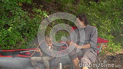 Ein junger Mann und sein kleiner Sohn haben eine Feuerpause Sie sitzen vor einem großen aufblasbaren Kajak stock footage