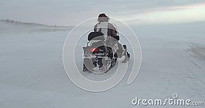Ein junger Reisender, der ein Schneemobil fahrung über einem See in Yamal fährt Expedition 2016 Geschossen von hinten Rote episch stock footage