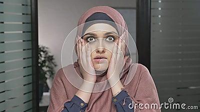 Ein junges arabisches Mädchen im roten hijab ist überrascht, ein Gefühl der Überraschung zeigt Betrachtet die Kamera, Porträt 60  stock video footage