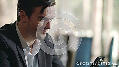 Ein lächelnder Geschäftsmann, der gute Nachrichten in Smartphone im Restaurant liest stock video