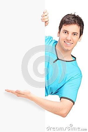 Ein lächelnder hübscher Mann, der hinter ein Panel gestikuliert