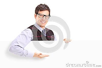 Ein lächelnder stattlicher Kerl, der auf ein weißes Panel gestikuliert