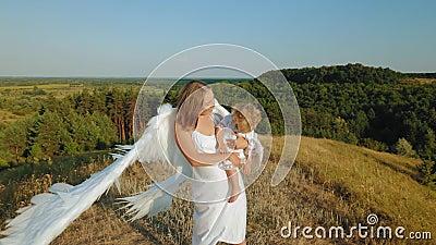 Ein Mädchen mit einem Kind in ihren Armen wird wie Engel gekleidet stock video footage