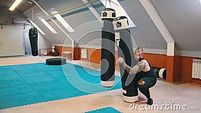Ein männlicher Bodybuilder hebt auf und trägt den Stanzbeutel auf die Schulter und setzt sich beim Gehen stock video footage