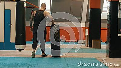 Ein männlicher Bodybuilder rollt einen großen Reifen im Fitnessraum stock footage