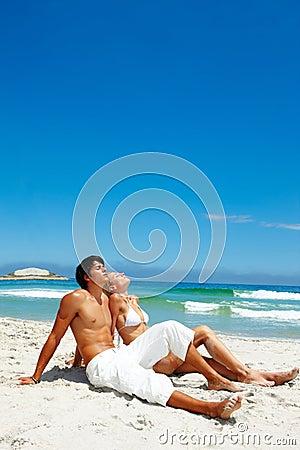 Ein müdes junges Paar, das auf dem Strand stillsteht