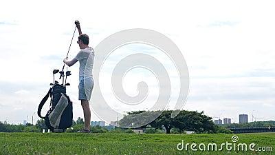 Ein Mann übt Tritte mit einem Golfclub auf einem Kurs stock video footage