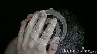 Ein Mann berührt sein Haar auf seinem Kopf, gegen einen schwarzen Hintergrund - 3 Das Haar eines Mannes ist grau stock video footage