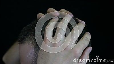 Ein Mann berührt sein Haar auf seinem Kopf, gegen einen schwarzen Hintergrund - 2 Das Haar eines Mannes ist grau stock footage