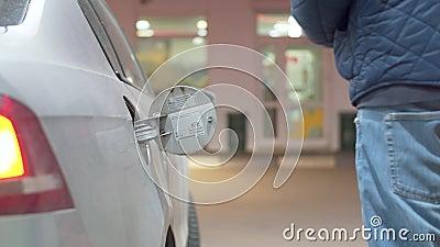 Ein Mann, der ein Auto betankt stock footage