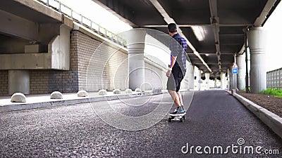 Ein Mann, der ein Skateboard auf den Asphalt auf dem Hintergrund der Überführung reitet stock footage