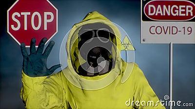 Ein Mann in einem gelben Hasmat-Anzug macht eine Stopphandgeste Coronavirus, SARS-nCOV-2, COVID-19, 2019-nCOV-Ausschreibung stock video footage