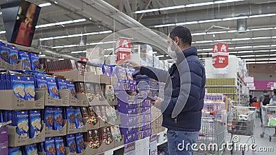 Ein Mann in einer blauen Jacke wählt ein Kind oder eine Ehefrau in einem Ladenlayout eine Schokoladenbar Ein Mann in einer Schutz stock footage