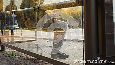 Ein Mann an einer Haltestelle der öffentlichen Verkehrsmittel wartet auf einen Bus Ein Mann nutzt mobiles Internet, während er au stock video