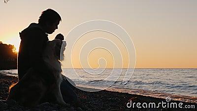 Ein Mann sitzt nahe bei seinem Hund und zusammen passt den Sonnenuntergang über dem See oder dem Meer auf stock video footage