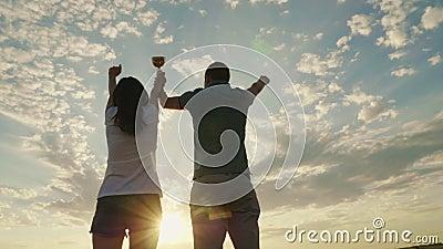 Ein Mann und eine Frau heben ihre Hände mit dem Meister ` s Cup an Sieg und Erfolg stock video footage