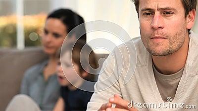 Ein Mann worring, während seine Familie auf dem Sofa ist stock footage