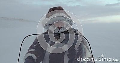 Ein Porträt eines müden Reisenden mit einem Haubenpelz auf einem Schneemobil fahrung YAMAL-Expedition 2016 Rote Kino-Kamera des E stock footage