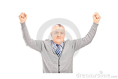 Ein reifer Herr gesetzt auf einer Tabelle, die Glück gestikuliert