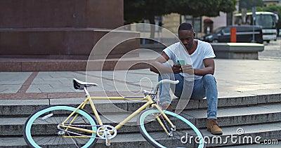 Ein schöner afrikanischer junger Mann mit seinem Smartphone, überprüft Nachrichten, sieht ernstlich aus, wenn er auf Ständen in d stock footage