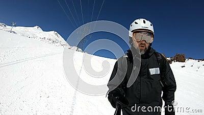 Ein selfie männlicher WeitwinkelSkifahrer gealtert in der schwarzen Ausrüstung und in den weißen Sturzhelmfahrten auf eine schnee stock video footage