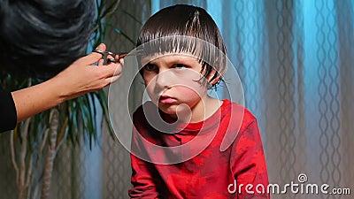 Ein seriöses Kind, das von einem Friseur auf den Frisör geschnitten wird stock video footage