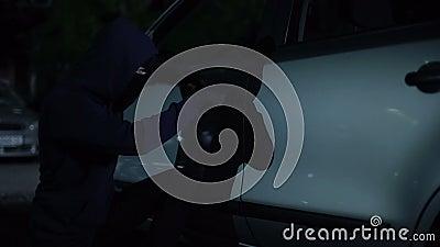 Einbrecher, der Auto entriegelt und nach innen, kriminelle Aktivität nachts, Sicherheit sitzt stock footage