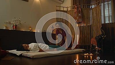 Eine asiatische Frau führt eine traditionelle thailändische Massage auf der Rückseite eines schönen europäischen Mädchens auf Chi stock video