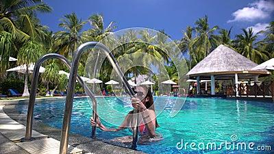 Eine dünne junge Frau, die das Schwimmen im Pool auf einem tropischen Erholungsort genießt stock video footage