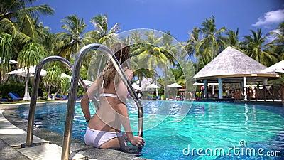 Eine dünne junge Frau, die das Schwimmen im Pool auf einem tropischen Erholungsort genießt stock video