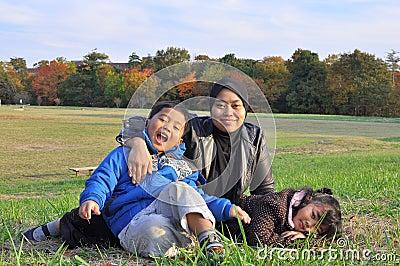 Eine Familie, die auf Gras während des Herbstes liegt und sitzt
