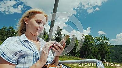 Eine Frau benutzt einen Smartphone, Fahrten in der offenen Kabine der Drahtseilbahn Im Urlaub in Zusammenhang mit dem Konzept stock video footage