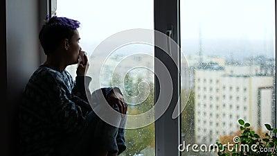Eine Frau hat eine laufende Nase Ein junges Mädchen sitzt nahe einem Fenster, es das ` s, das draußen regnet tiefstand stock footage