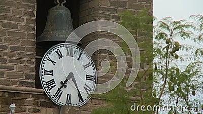 Eine Glocke und eine Uhr im Fokus stock footage
