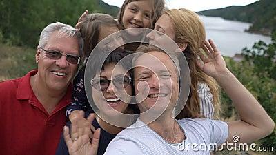 Eine große glückliche Familie nimmt ein selfie oder benutzt Telefon Videoanruf-Kamera auf der Seeküste stock footage
