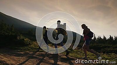Eine Gruppe Freunde mit Rucksäcken steigt oben der Berg In den Strahlen der untergehenden Sonne Aktiver Lebensstil stock video