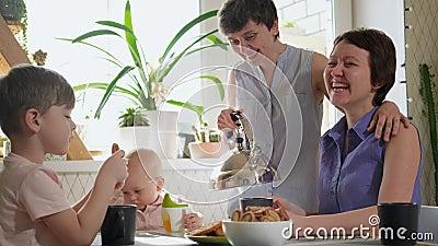 Eine homosexuelle lesbische Familie mit zwei Kindern und Müttern sitzt in der Küche am Tisch und frühstücken Lifestyle stock video