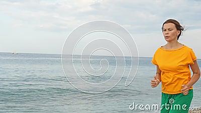 Eine junge Frau joggt am Sandstrand stock video footage
