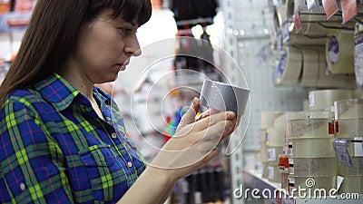 Eine junge Frau wählt und kauft einen Grau metallisierten Klebstreifen im Supermarkt stock video footage
