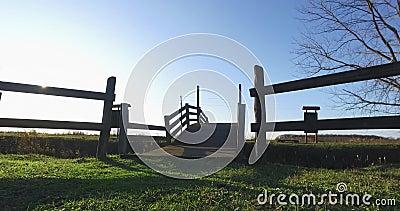 Eine kleine Holzbrücke über den Kanal, eine Momentaufnahme der Umgebung mit blauem Himmel im Hintergrund stock video