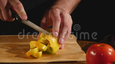 Eine Koch ` s Hand schneidet einen grünen Pfeffer durch ein Messer auf einem Schneidebrett stock footage