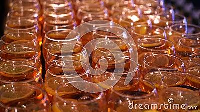 Eine Menge Blütengläser an der Bartheke Oranorangefarbenes Getränk mit orangefarbenem Innencocktailglas stock video