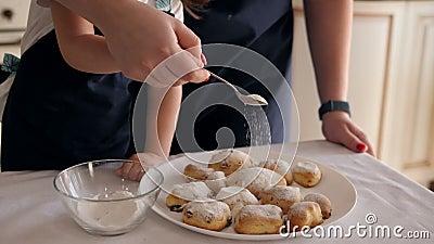 Eine Mutter mit einer kleinen Tochter, bestreut mit Zuckerpulver leckeren Keksen stock footage