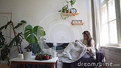 Eine schöne Frau in einem weißen Pulater nähert sich dem Sofa und lügt, Ruhe und Entspannung. Zuhause und Frieden stock footage