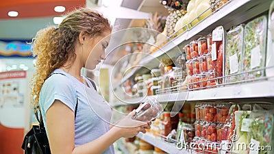 Eine weibliche Person wählen Produkte im Großen Markt stock video