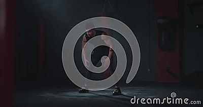 In einem dunklen Fitnessstudio Fitness Körper junge Mann sehr attraktiv starten seine Ausbildung mit einer Aerobic-Übung vor eine stock video