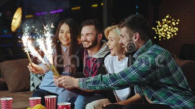 In einer modernen Loft-Wohnung treffen sich zwei Paare, um etwas im Wohnzimmer auf dem Sofa zu feiern, das sie nehmen stock video