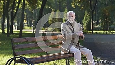 Einsamer umgekippter alter Mann, der allein im Park sitzt und an das Leben, Pensionär denkt stock video