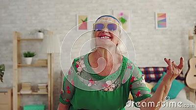 Eje de balancín alegre del pensionista de la mujer mayor con el pelo gris en los vidrios que miran la cámara MES lento almacen de video